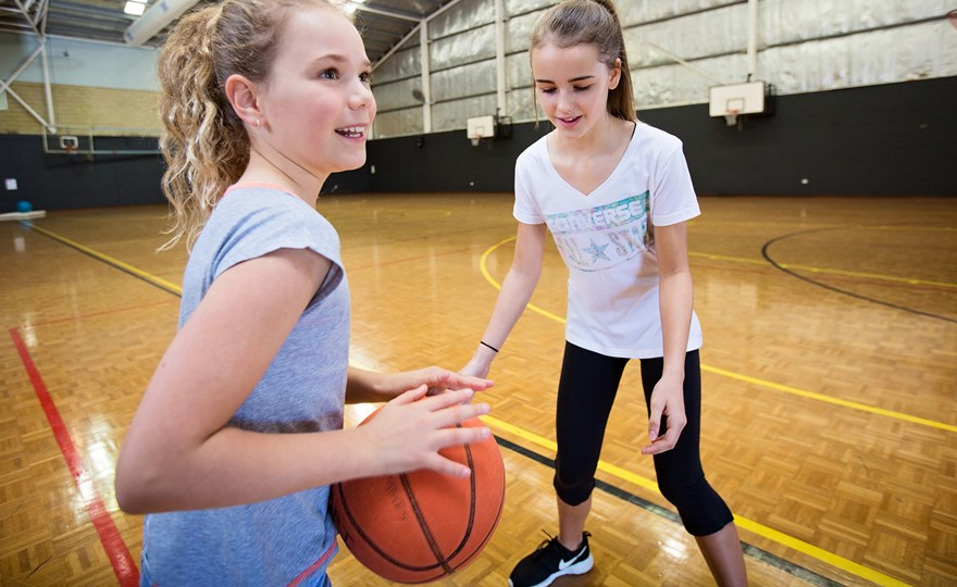 Girls playing basketball in indoor courts at HBF Stadium