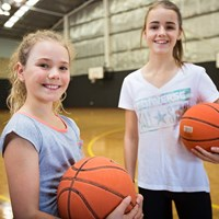 Girls holding basketballs at HBF Stadium