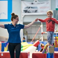 Boy and instructor gymnastics lessons