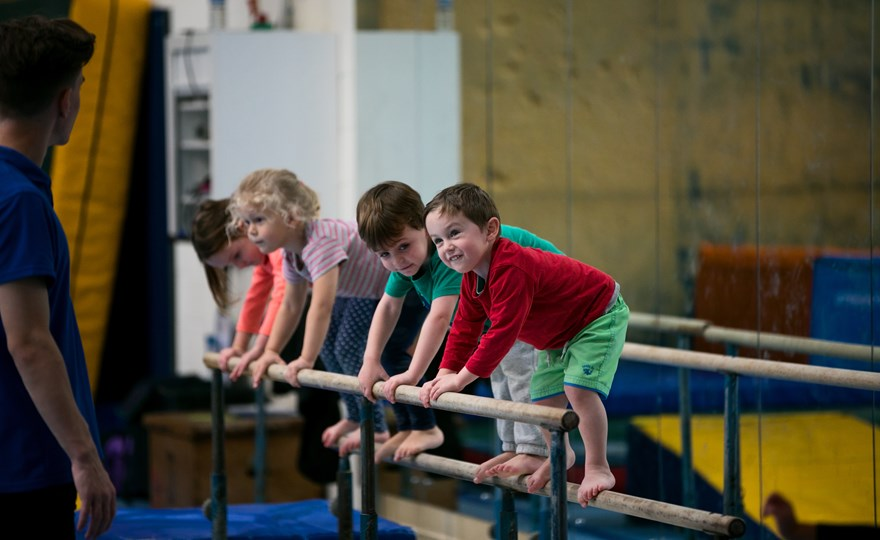 Kids lined up on gymnastics beam at HBF Stadium