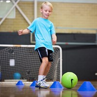 Boy kicking soccer ball at HBF Arena