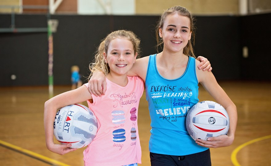 Young girls smiling holding basketballs HBF Arena